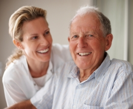 Closeup portrait of a happy senior man on a wheel chair with a nurse for assistance